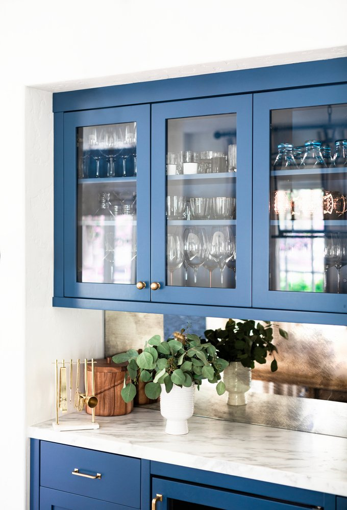 kitchen area with blue painted cabinets with glassware inside