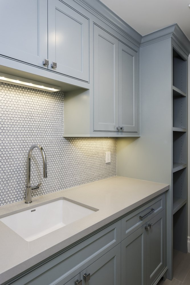 laundry room with custom blue grey shelves and sink